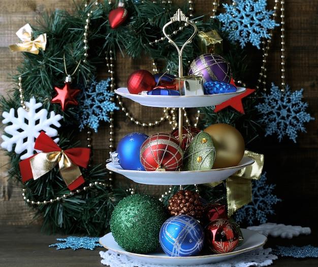 Weihnachtsdekoration auf dessertständer, auf farbiger holzoberfläche