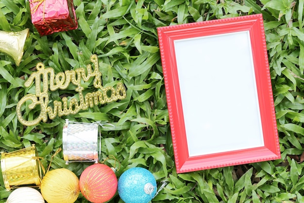 Weihnachtsdekoration auf einem grünen rasen und haben goldtext von frohen weihnachten.