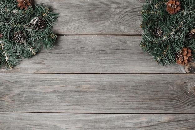 Weihnachtsdekoration auf rustikaler hölzerner tischoberfläche. fichtenzweig mit perlengewindeseitenanordnung.