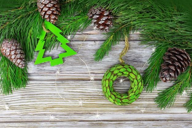 Weihnachtsdekoration auf tannenzweigen. natürliche zapfen und holzspielzeug auf schmutzholzhintergrund. draufsicht und kopierraum.