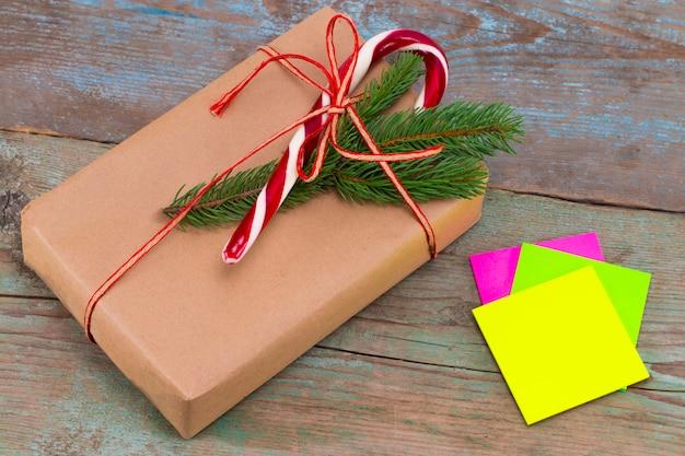 Weihnachtsdekoration. boxen mit weihnachtsgeschenken mit haftnotiz. schöne verpackung. weinlesegeschenkbox auf hölzernem hintergrund. handgemacht