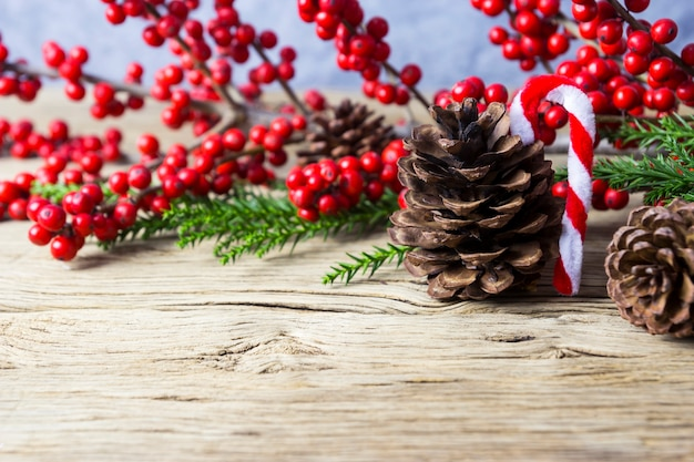 Weihnachtsdekoration des kiefernkegels und des roten winterberry auf altem holz