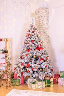 Weihnachtsdekoration des wohnzimmers die dekoration des raumes weihnachten schneebedeckter tannenbaum mit spielzeuggeschenk