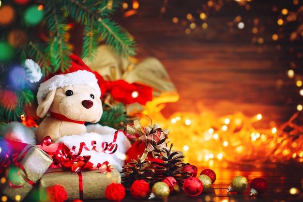 Weihnachtsdekoration, feiertagsplüschhund mit geschenken unter dem weihnachtsbaum. mit neujahr und weihnachten.