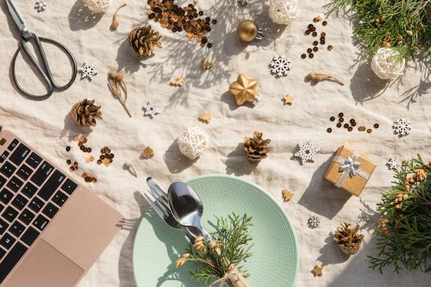 Weihnachtsdekoration. festliche platte und tischbesteck, laptop mit weihnachtsdekorationen am sonnigen tag. feiertag, neues jahr, hartes licht mit schatten
