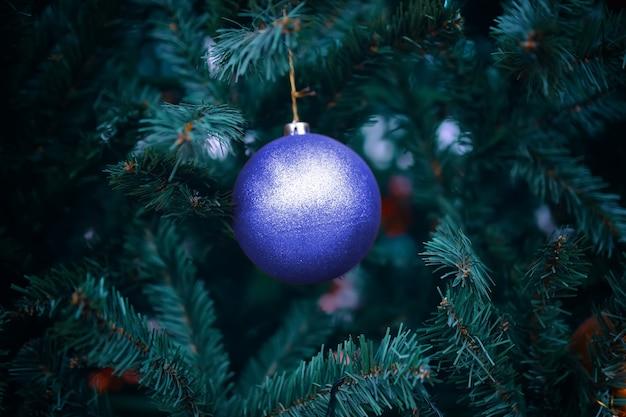 Weihnachtsdekoration für den urlaub. lila kugel auf weihnachtsbaum.