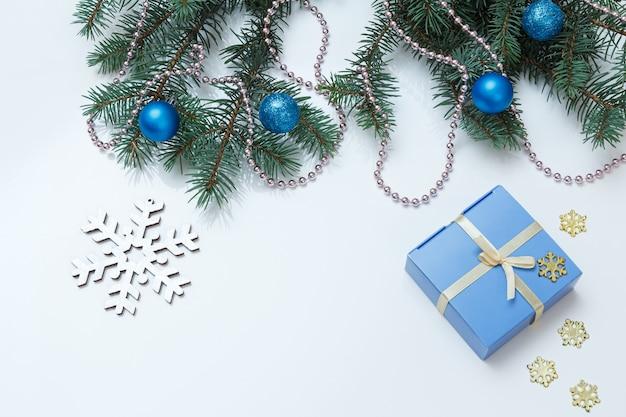 Weihnachtsdekoration. geschenkbox, tannenbaumzweige mit kugeln auf dem weißen hintergrund. ansicht von oben. weihnachtsgrußkartenkonzept.
