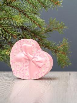 Weihnachtsdekoration. geschenkbox und ein tannenbaumzweig auf dem grauen hintergrund. weihnachtsgrußkartenkonzept.