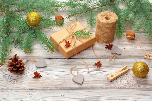 Weihnachtsdekoration, geschenkbox und kieferniederlassungen auf hölzernem hintergrund