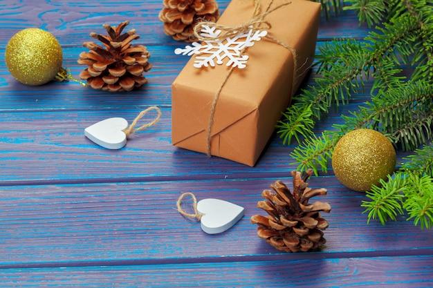 Weihnachtsdekoration, geschenkbox und kieferniederlassungen auf hölzernem