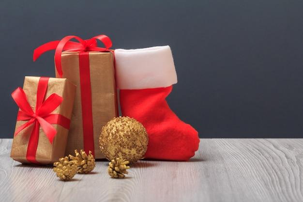 Weihnachtsdekoration. geschenkboxen, santa's boot, ein spielzeugball und ein natürlicher tannenzweig auf grauem hintergrund. weihnachtsgrußkartenkonzept.