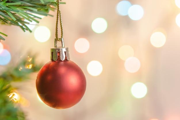 Weihnachtsdekoration. hängende rote bälle auf kiefernniederlassungen weihnachtsbaumgirlande und -verzierungen über abstraktem bokeh hintergrund mit copyspace
