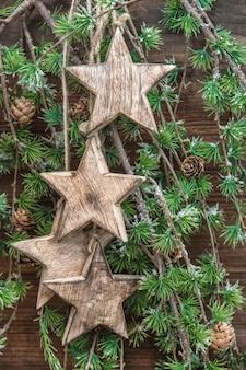 Weihnachtsdekoration holzsterne und kiefernzweige. feiertage hintergrund