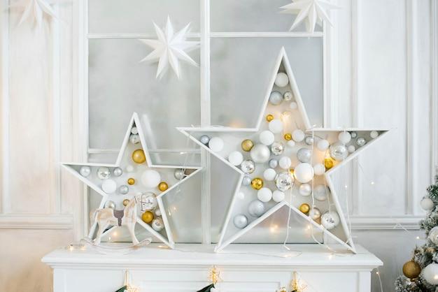 Weihnachtsdekoration im wohnzimmer: sterne mit gefüllten weihnachtskugeln