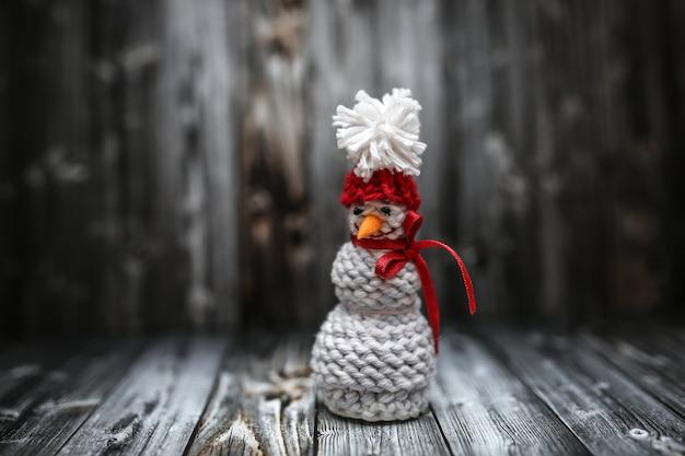 Weihnachtsdekoration in der weinlese, die auf schwarzem hintergrund mit strickendem schneemann tont.