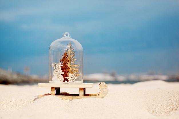 Weihnachtsdekoration in form einer glaskugel mit einem weihnachtsbaum und einem schneemann am strand