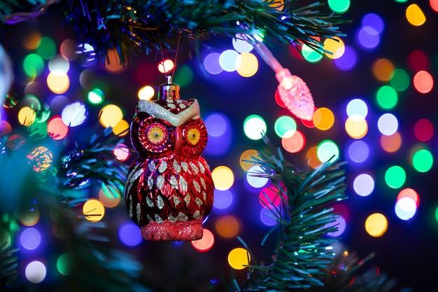 Weihnachtsdekoration in form einer roten eule, die an einem weihnachtsbaum im hintergrund hängt, glühen viele girlanden in den verschiedenen farben.