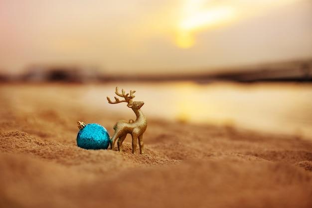 Weihnachtsdekoration in form eines goldenen hirsches und eines balls am strand