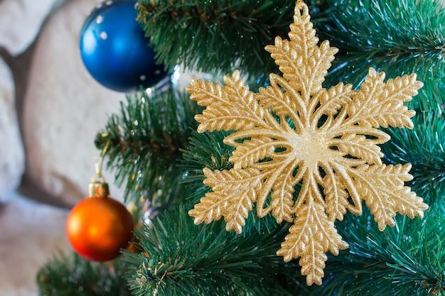 Weihnachtsdekoration in form von goldenen schneeflocken nah oben und andere spielwaren auf dem weihnachtsbaum