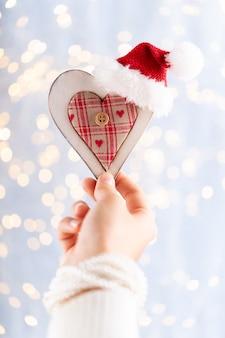 Weihnachtsdekoration in frauenhand. weihnachtsgrußkarte. frauenhände halten weihnachts- oder neujahrsgeschenk.