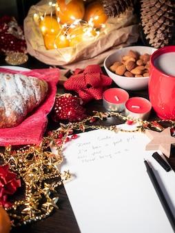 Weihnachtsdekoration mit begonnenem brief an den weihnachtsmann auf dem tisch