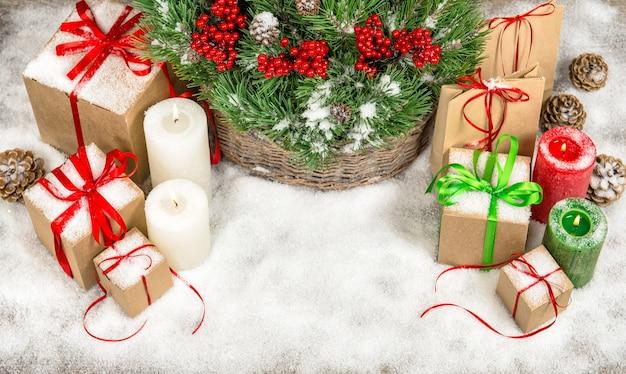 Weihnachtsdekoration mit brennenden kerzen und geschenkboxen. tannenzweige im korb