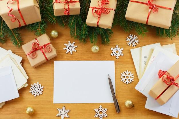 Weihnachtsdekoration mit geschenktüten und leerem notizbuch