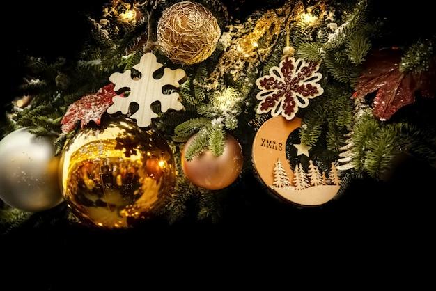 Weihnachtsdekoration mit goldenen kugeln und hölzernen schneeflocken und tannenzweigen auf schwarzem hintergrund. frohe weihnachten und ein frohes neues jahr postkartenhintergrund