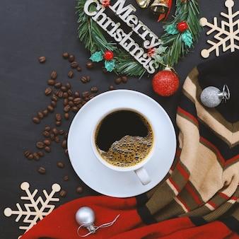 Weihnachtsdekoration mit heißem kaffee auf schwarzem hölzernem hintergrund. flach liegen. kopierplatz für text.