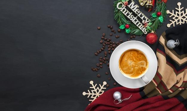 Weihnachtsdekoration mit heißem kaffee und bohnen auf schwarzem hölzernem hintergrund. f