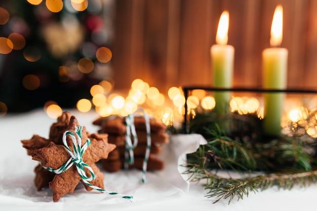 Weihnachtsdekoration mit kerzen, tannenzweigen und lebkuchen