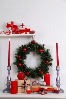Weihnachtsdekoration mit kranz, kerzen und geschenkboxen auf regal auf weißer wand