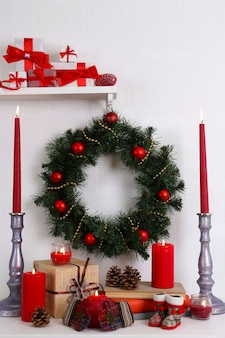 Weihnachtsdekoration mit kranz, kerzen und geschenkboxen im regal an weißer wand