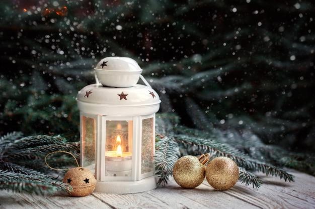 Weihnachtsdekoration mit laterne, goldschneeflocke und bällen, tannenzweigen und verzierungen auf dunklem hintergrund.
