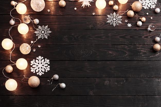 Weihnachtsdekoration mit lichtern auf dunklem holz