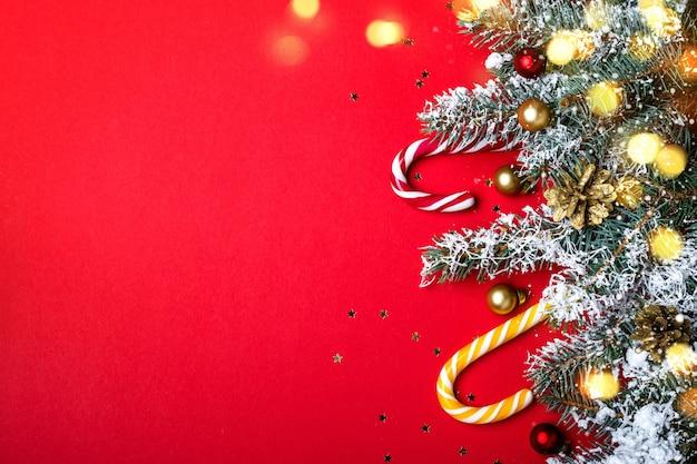 Weihnachtsdekoration mit nadelbordüre und zuckerstangen neben leuchtenden lichtern
