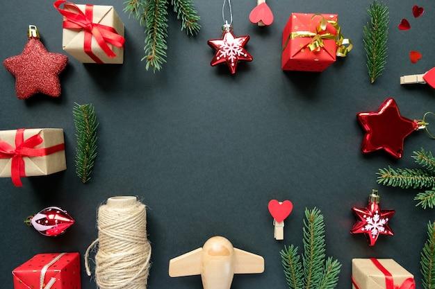 Weihnachtsdekoration mit niederlassungen, sternen und geschenkboxen auf schwarzem rahmenhintergrund