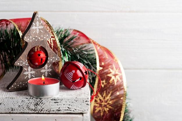 Weihnachtsdekoration mit roten glöckchen und kerze auf weißer rustikaler oberfläche