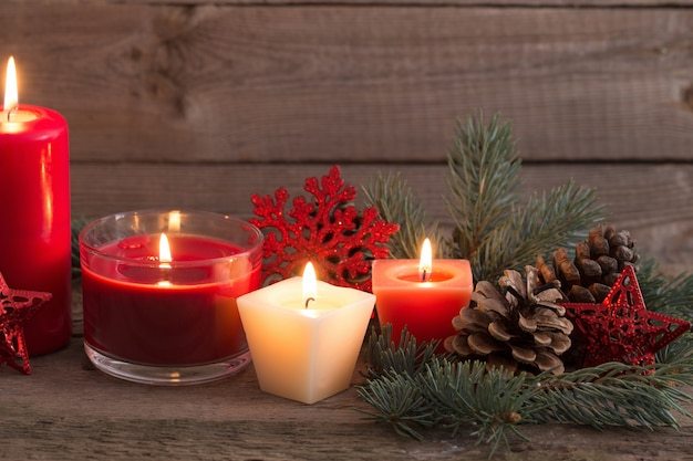 Weihnachtsdekoration mit roten kerzen auf hölzernem hintergrund