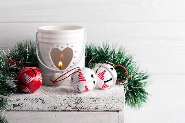 Weihnachtsdekoration mit roten und weißen klingelglocken und kerze auf weißem rustikalem hintergrund