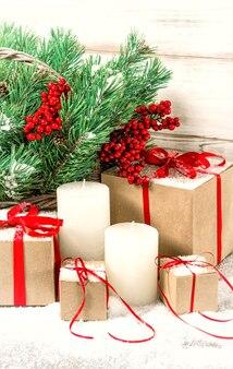 Weihnachtsdekoration mit weißen kerzen, geschenkboxen und kiefernzweigen. getöntes foto im vintage-stil