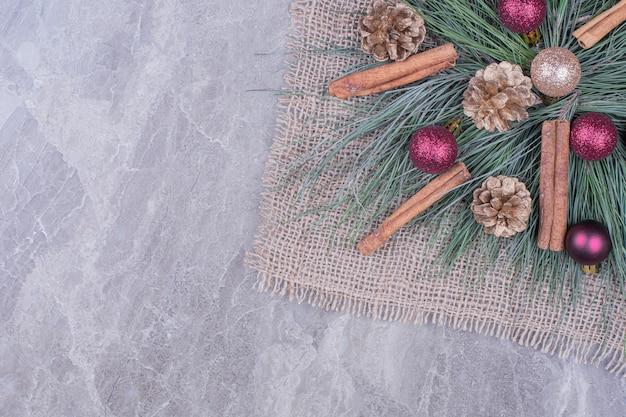 Weihnachtsdekoration mit zimt, zapfen und eichenzweigen