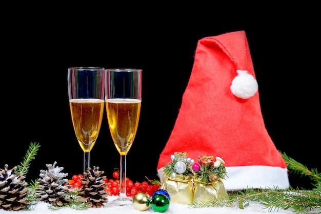 Weihnachtsdekoration mit zwei gläsern champagner, weihnachtsmann-hut