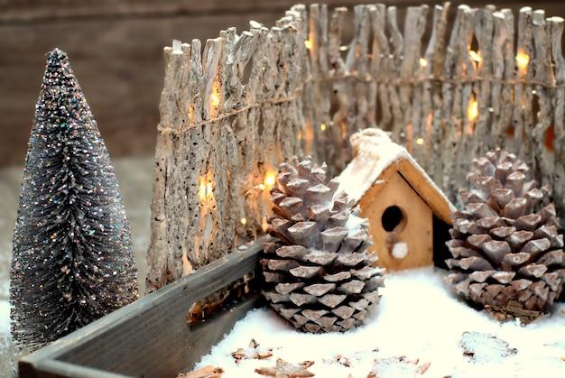Weihnachtsdekoration-nahes hohes vogelhaus, kegel und zaun mit glühlampen.