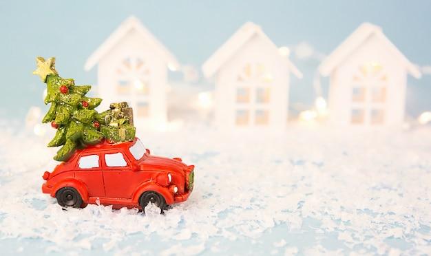 Weihnachtsdekoration - rotes retro-auto auf schnee trägt weihnachtsbaum in der nähe von häusern