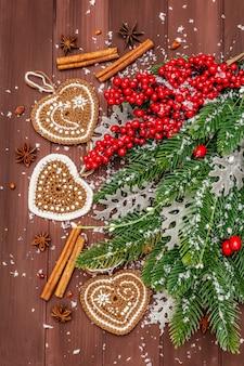 Weihnachtsdekoration. tannenbaum des neuen jahres, frische blätter, gehäkelte ingwerplätzchenherzen, gewürze und künstlicher schnee.