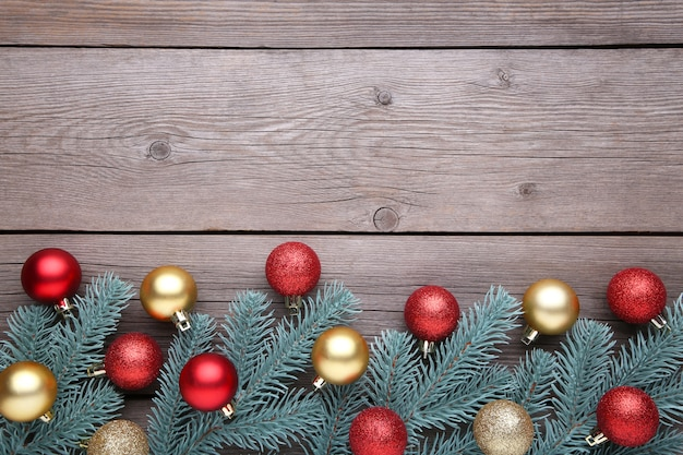 Weihnachtsdekoration. tannenbaumniederlassung mit bällen, kleinen geschenken und bögen auf einem grauen hintergrund