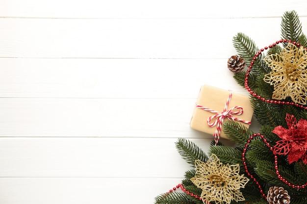 Weihnachtsdekoration. tannenbaumniederlassung mit geschenk- und rot- und goldweihnachtsblumen auf weißem hintergrund