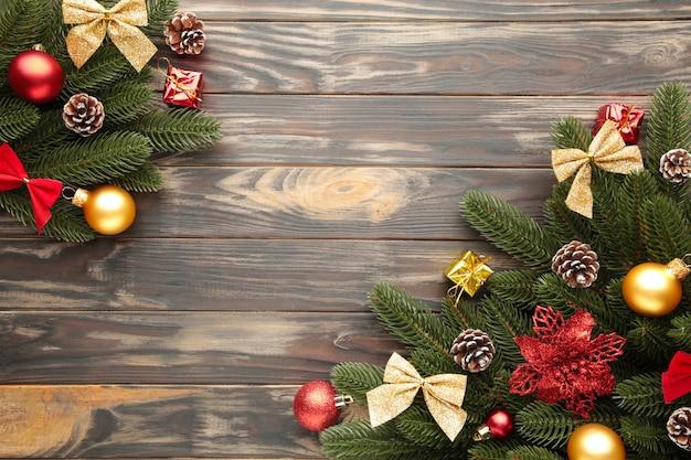 Weihnachtsdekoration. tannenbaumniederlassung mit rot und goldkugeln auf braunem hintergrund