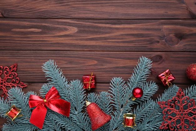 Weihnachtsdekoration. tannenbaumniederlassung mit roten bällen, kleinen geschenken und bögen auf braun